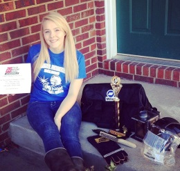 Chrissy posing with her gear and awards